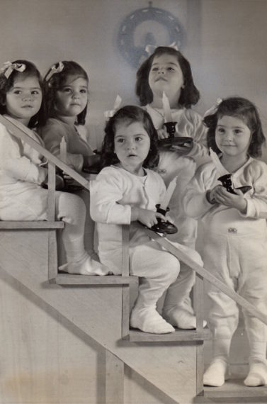 Annette, Yvonne, Cécile, Émilie, and Marie Dionne holding candles, 1938